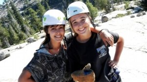 Two girls smiling and giving a thumbs up after rock climbing to the top