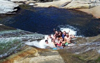 Church youth group sits together in the river durring a backpacking trip