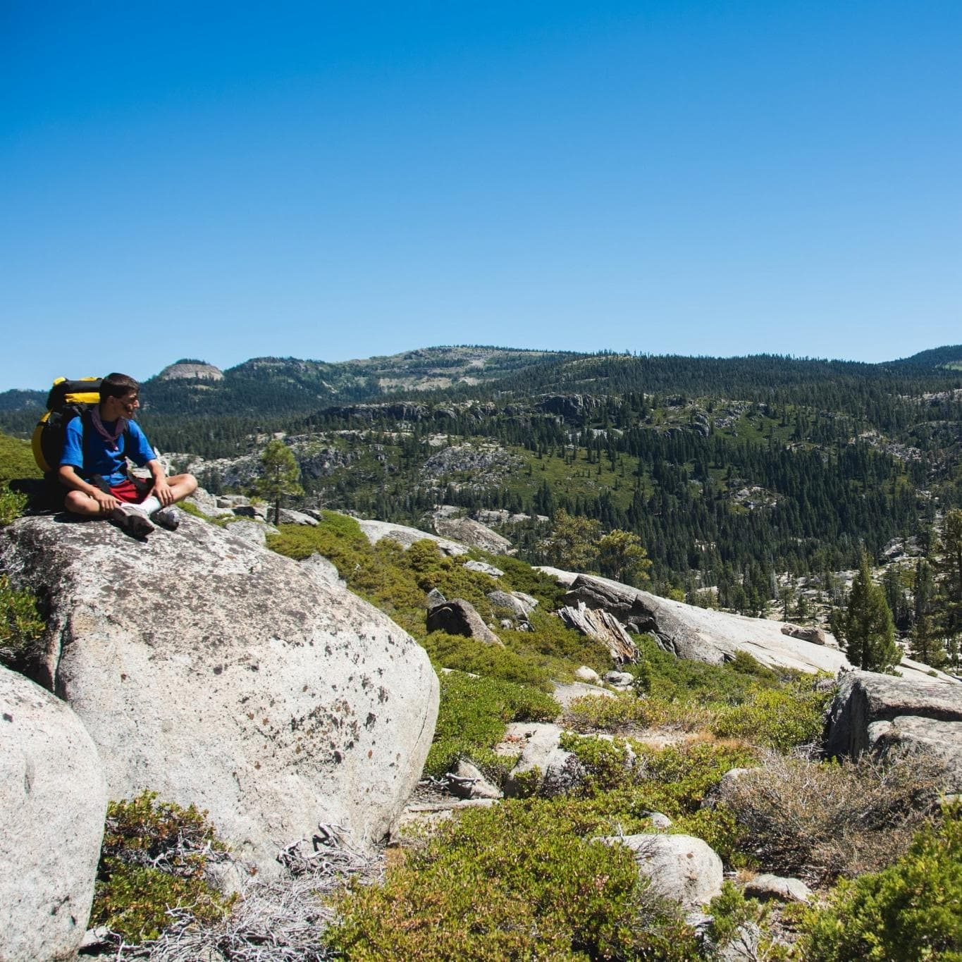 Backpacker sits on boulder overlooking wilderness valley
