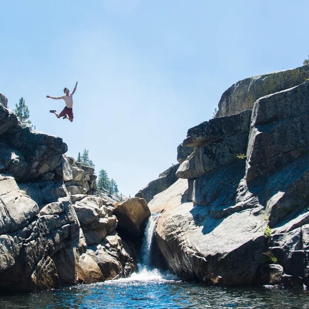 water filled canyon, walls 25 feet high, man cliff jumping