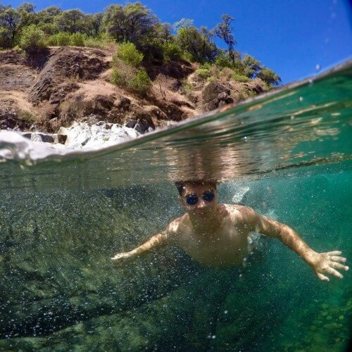 boy swims underwater with googles in canyon