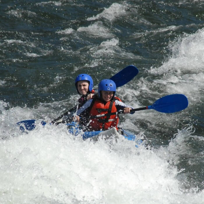 two in inflatable kayak approach large rapid