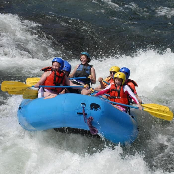blue whitewater raft in middle of a class 3 rapid