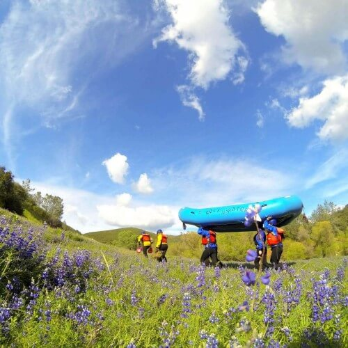 Rafters carry whitewater raft overhead in grassy field