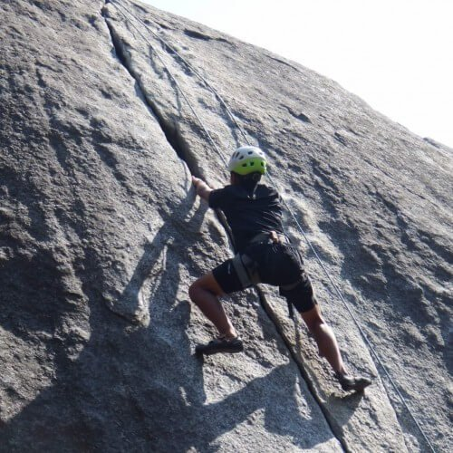 rock climber in helmet and harness climbs granite crack