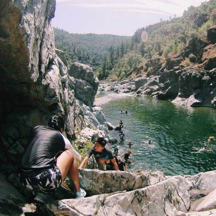 teens hike through rocky canyon with wide, calm river pools