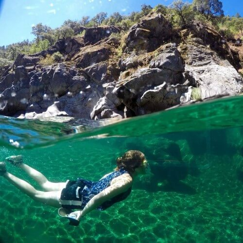 image above and below water surface with camper swimming in canyon