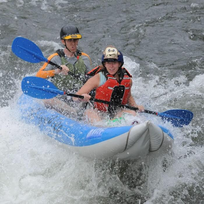 two paddlers in inflatable kayak run large whitewater rapid