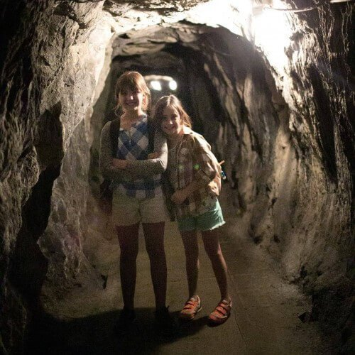 two smiling girls stand in gold mine underground