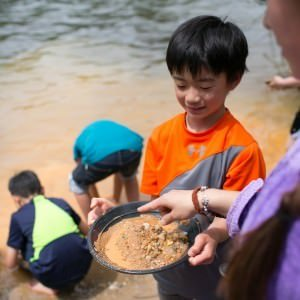 boy with pan full for dirt for gold panning by river