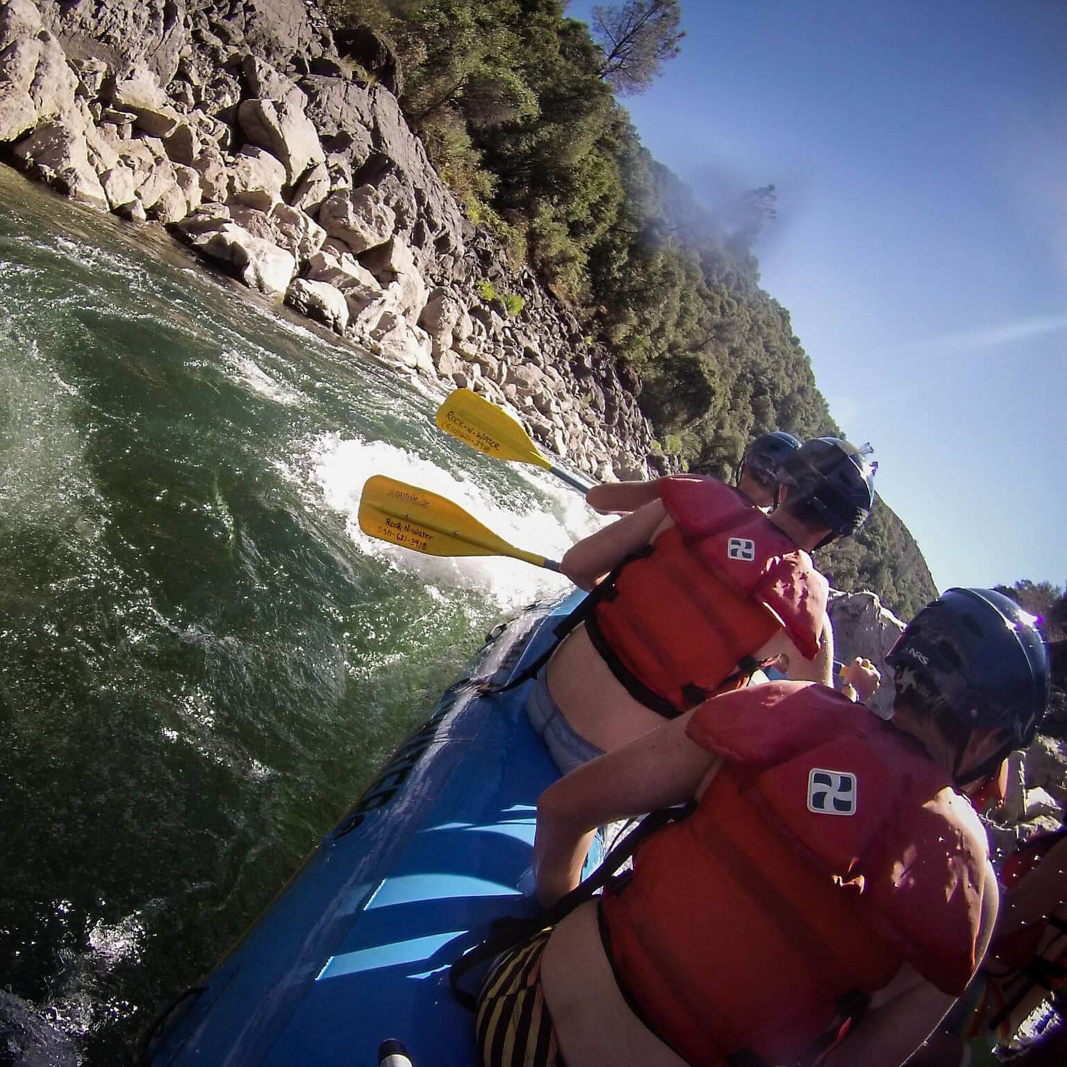 Point of view in blue whitewater raft on river