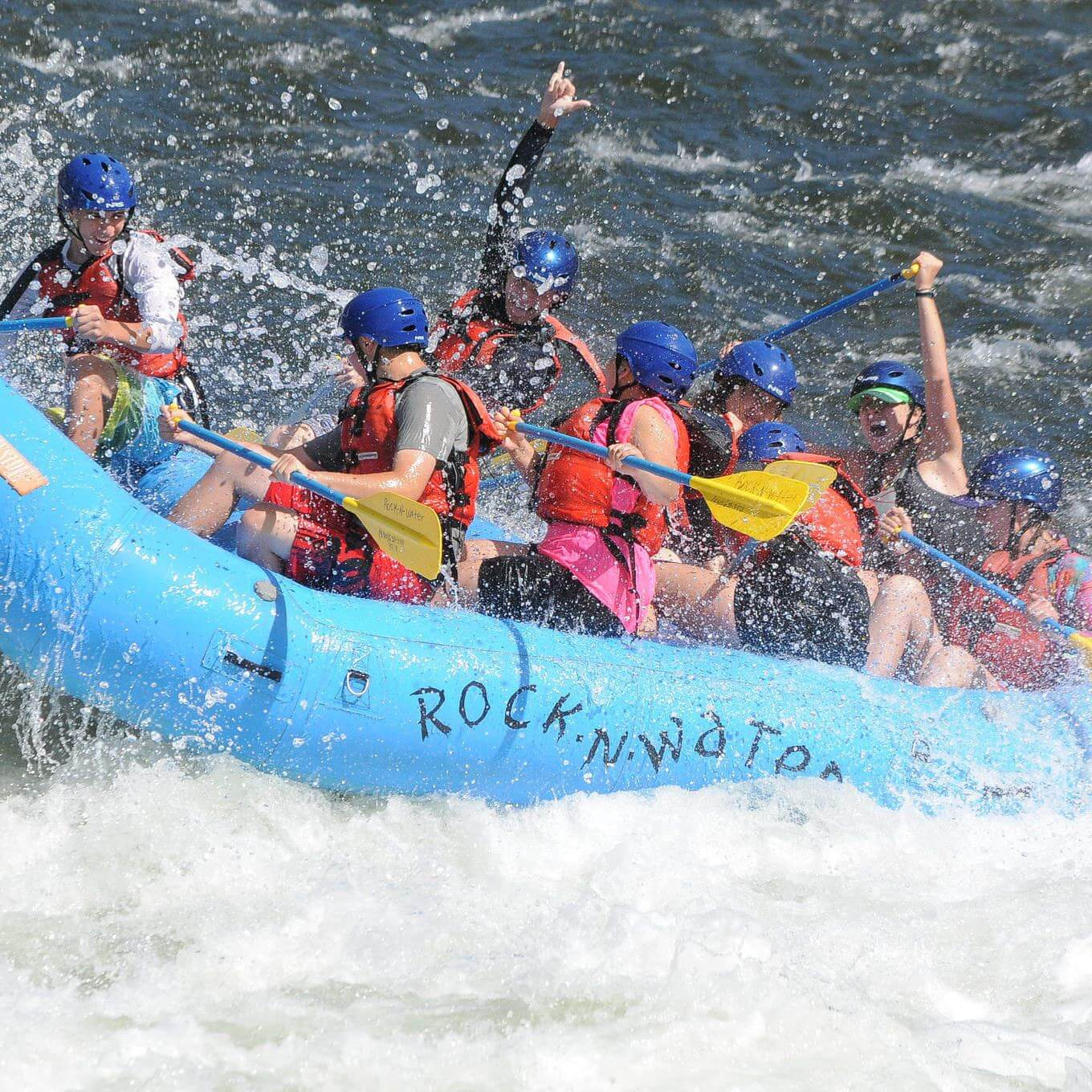 Whitewater raft splashing through river rapids with campers on board