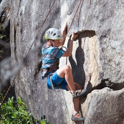 boy rock climbing on granite cliff with rope, harness, and helmet.