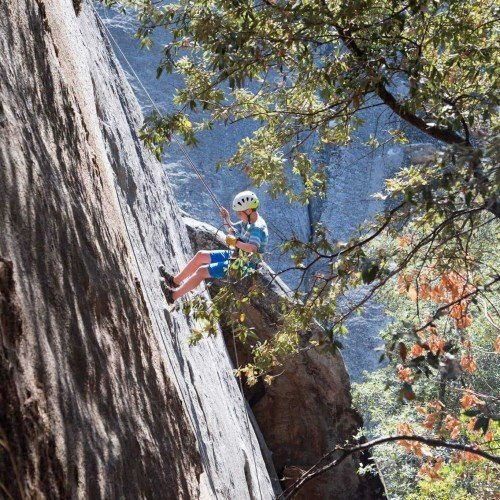 boy rappels off cliff with rope harness and helmet