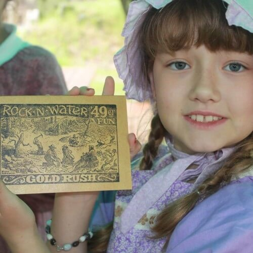 girl in 1850's costume holds christian camp logo