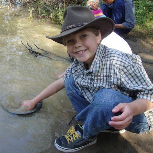 smiling boy gold panning in hat in river