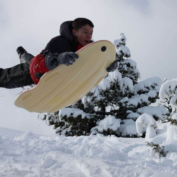 boy in air with sled in snow