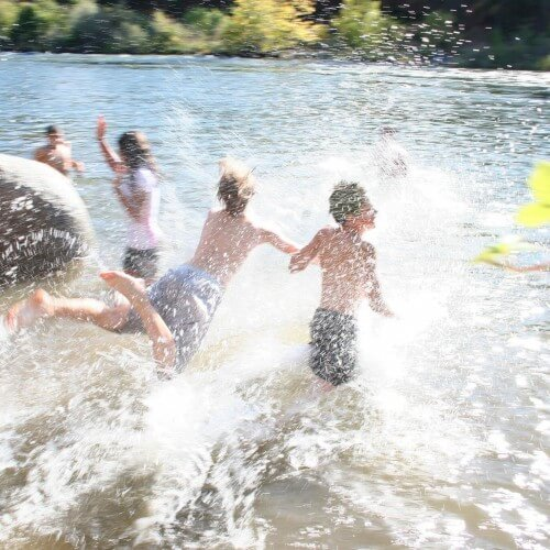 young boys jump in river at summer camp
