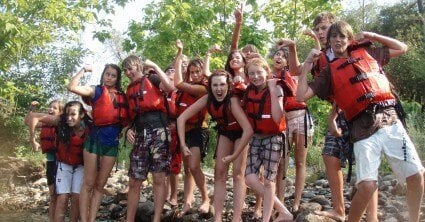 friends pose together before whitewater rafting at camp