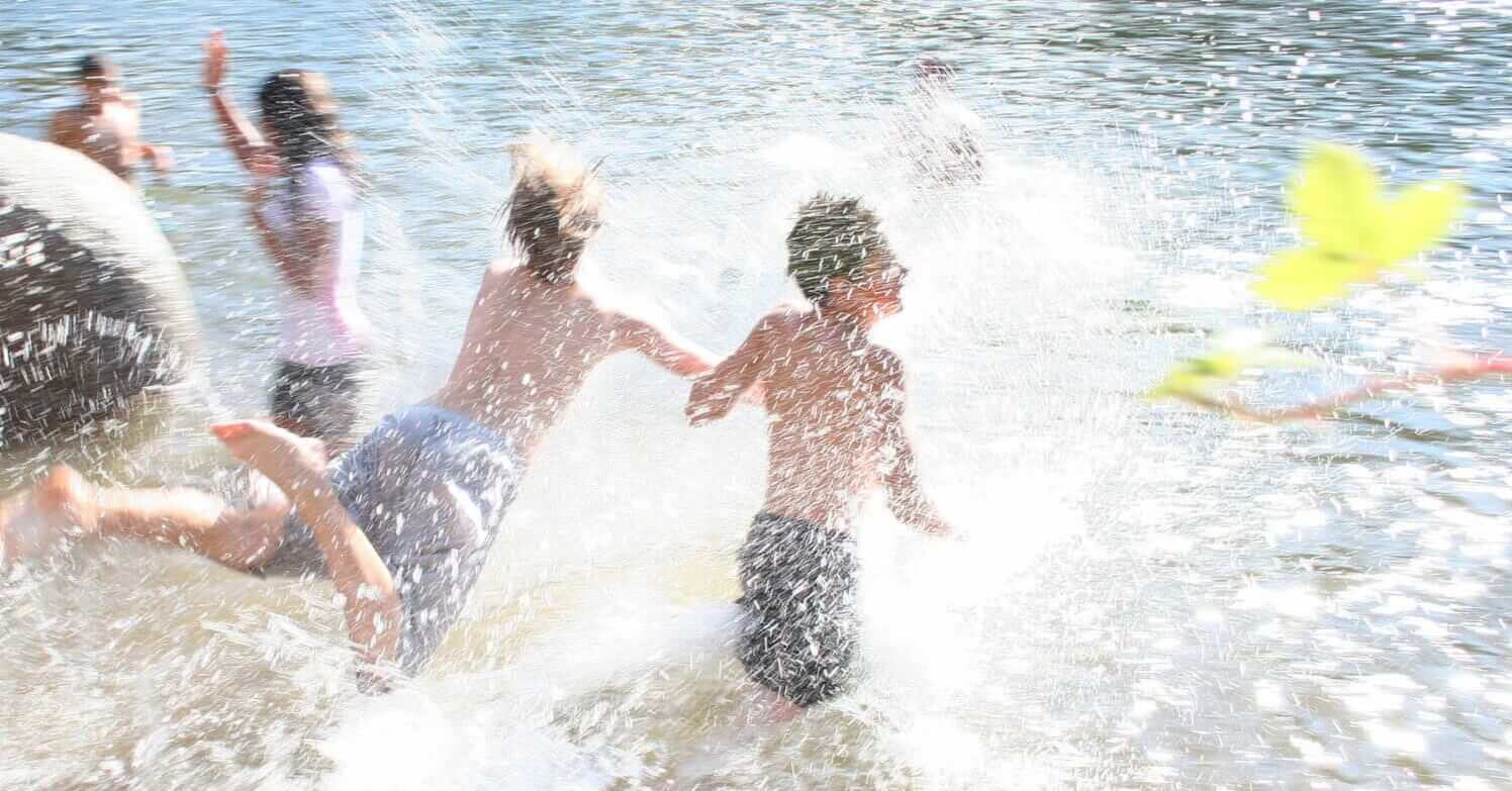 boys run and splash in river