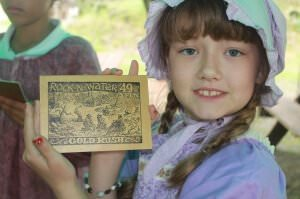 camper dressed for 1854 shows off the postcard she just made