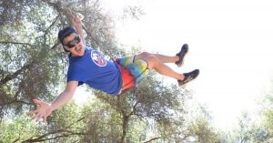 adult camper swinging high into the air at one of our camps for adults