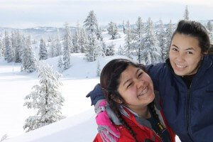 friends embrace overlooking snow covered mountains during their christian winter camp