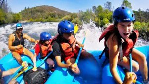 campers white water rafting in california at summer camp
