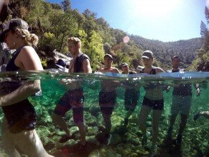teens walking through chest deep water in canyon