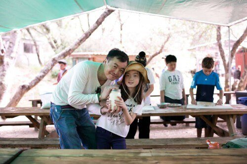 Father and daughter outside at picnic table on field trip