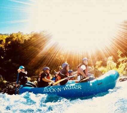 Seven campers whitewater rafting under bright sunshine